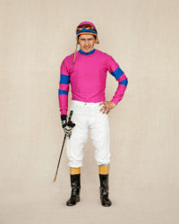 Jockey in magenta and blue. Standing proud at the race track in San Isidro, Argentina.
